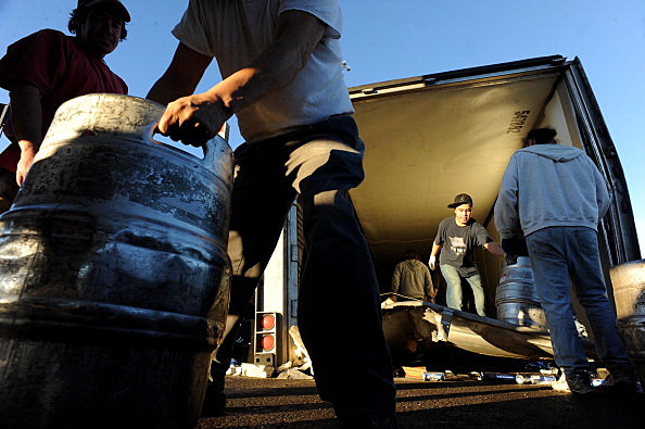 (HR) Troy Davis, left and Mike Mergel help load off kegs of beer with help from other crew members from Labor Ready at 74th and Federal who were hired to come clean up the scene. A 53 foot long semi-trailer truck carrying between 70-80,000 pounds of canne