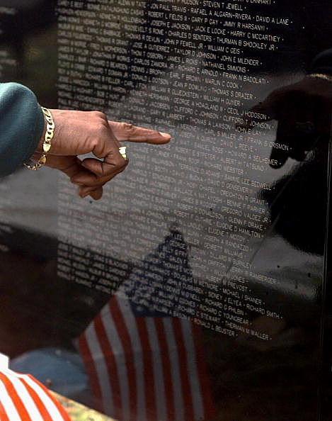 "Vietnam veteran points to names on surface of ""The Wall That"